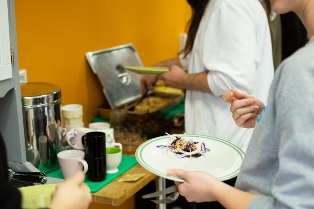 Deltagarna står i kö för att äta maten som lagats